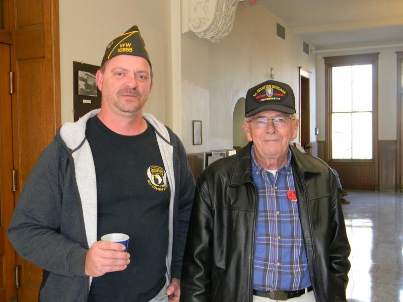 Two men stand beside each other, one in Airborne shirt and one in blue plaid, both with veterans' hats, in hallway of Court house